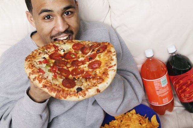 Man eating pizza, potato chips and soda bottles in the background.