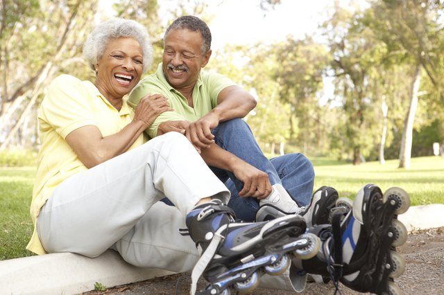 smiling elderly couple wearing rollerblades