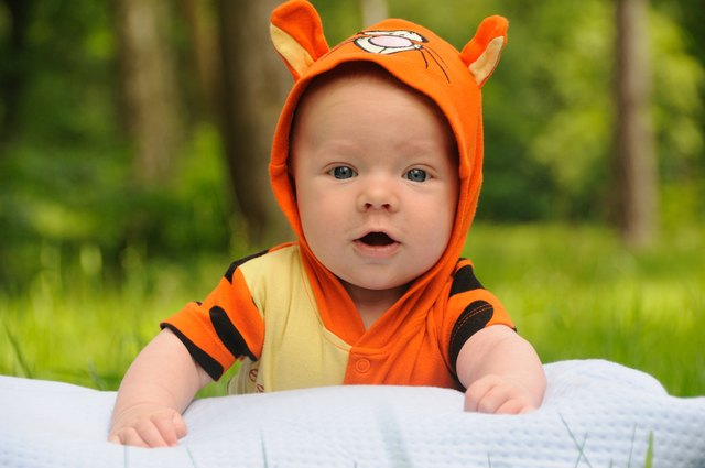 A baby boy wearing a tiger outfit lays on his belly on a blanket outside.