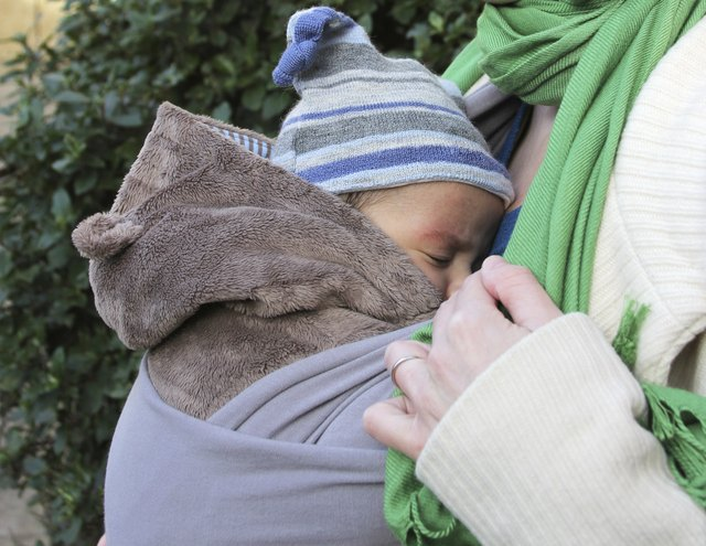 A baby sleeps in a sling on his mother's chest.