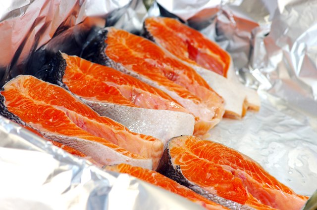 Raw salmon steaks being prepared for broiling