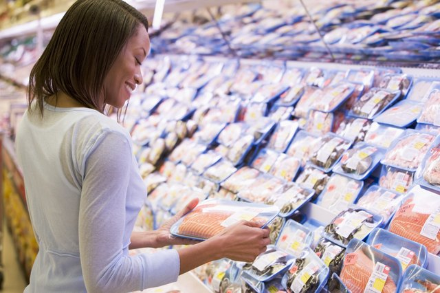 A woman chooses a pack of salmon at a grocery store.
