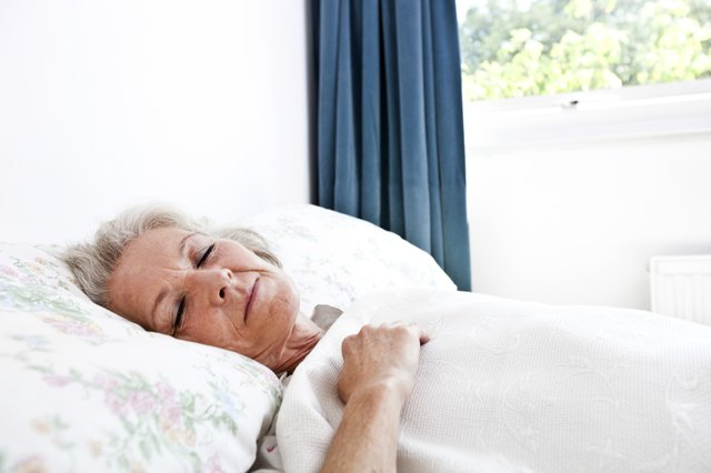 Senior woman sleeps with head propped up by pillows