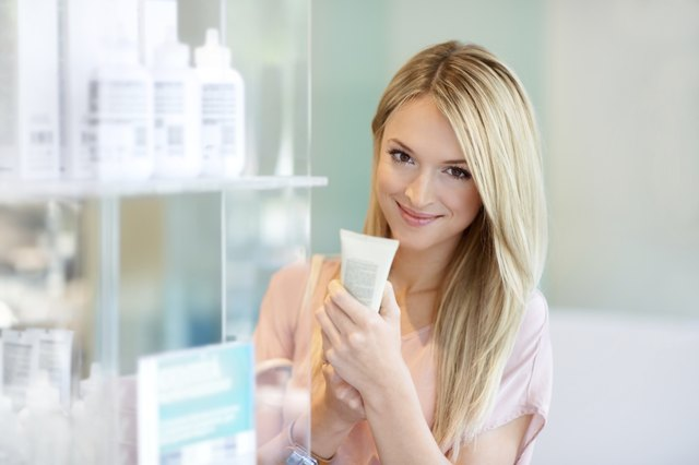 blonde woman looking at hair serum product