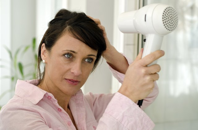woman blow drying hair after wash