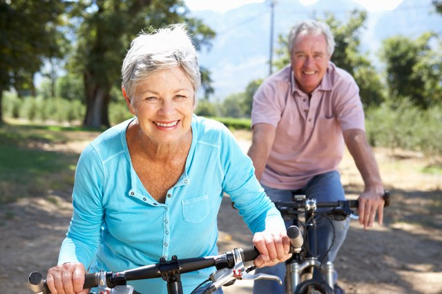 An energetic couple takes a bike ride together on a country road.