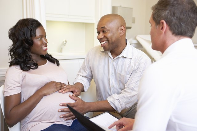 Pregnant wife and husband talking to doctor
