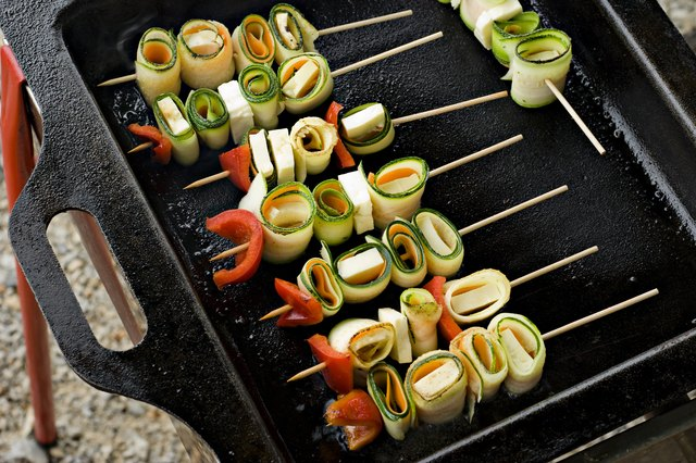 Colorful vegetable kabobs with tofu on a grill pan.