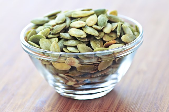 Pumpkin seeds in a glass dish on a table.