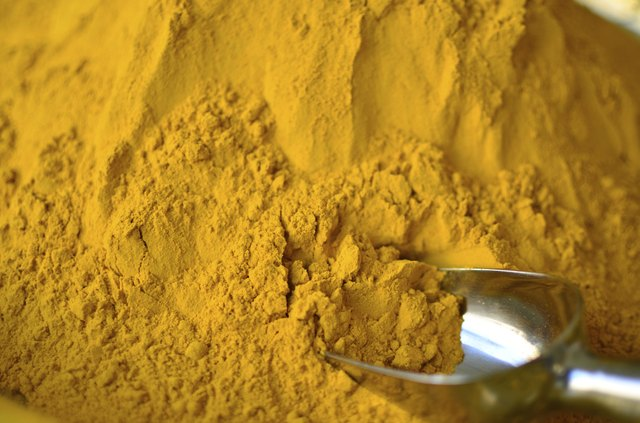pile of Turmeric powder with scoop