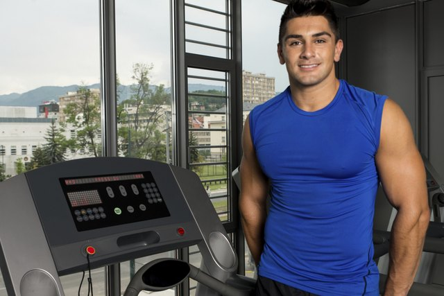 man standing beside treadmill in gym
