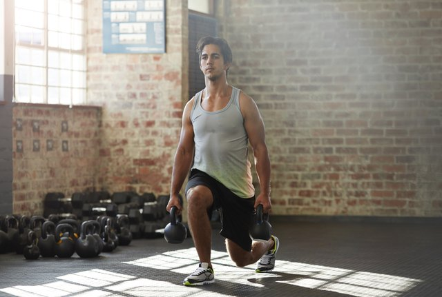Forward lunges using kettlebells in place of dumbbells