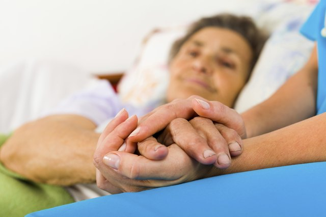 Nurse holding hand of a senior woman in the hospital