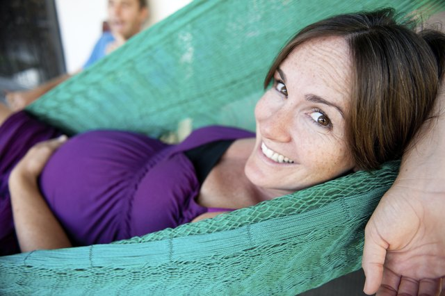 A healthy pregnant woman reclines in a hammock.