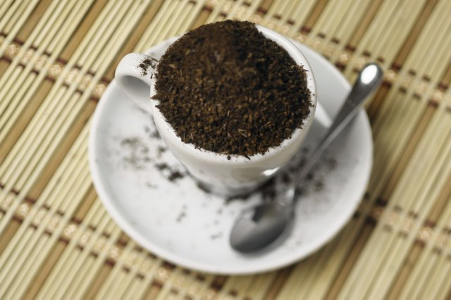 A coffee cup overflowing with coffee grounds on a bamboo mat.