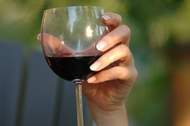 Woman's hand holding a glass of red wine
