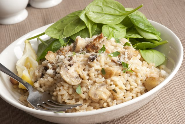 A bowl of brown rice risotta with a fresh spinach salad.
