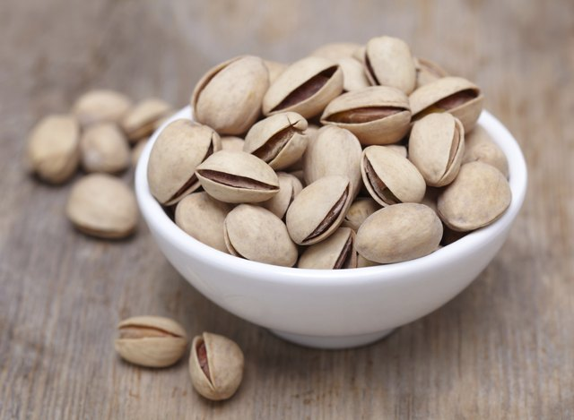 A small bowl of pistachio nuts on a wooden background.