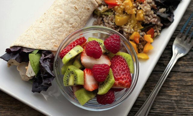 A chicken wrap with lettuce served with brown rice, vegetables, and a bowl of fruit.