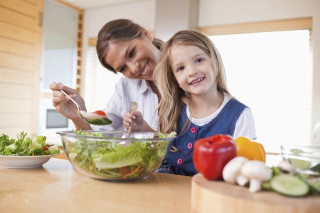 A girl helps her mother make a salad in the kitchen.