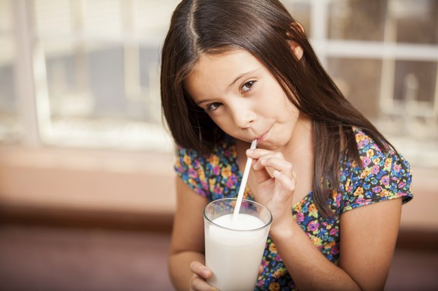 Young girl using straw to drink glass of milk