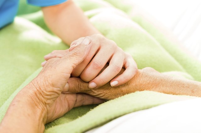 Close-up of a cancer patient holding a loved one's hand