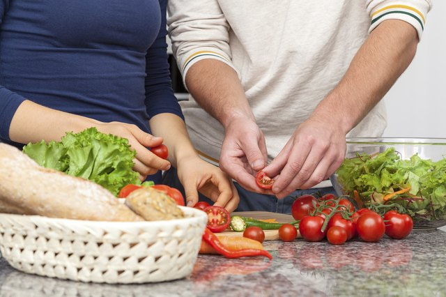 A couple prepares vegetables together in the kitchen.