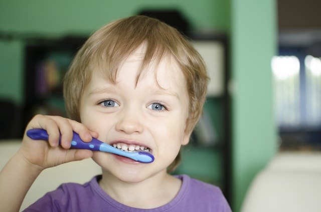 A small child brushes their teeth.