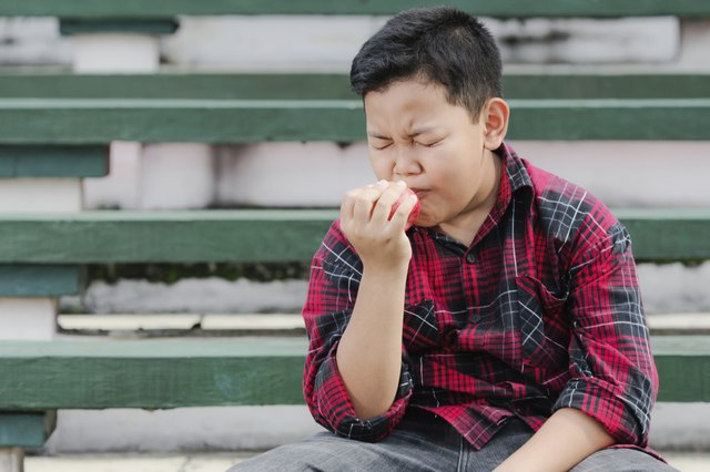 A boy experiencing pain while eating an apple.
