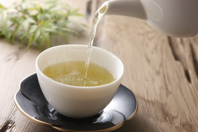 A cup of freshly poured green tea on a wooden table.