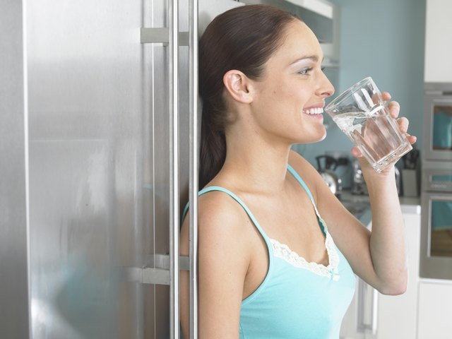 A woman drinking a glass of water in a kitchen