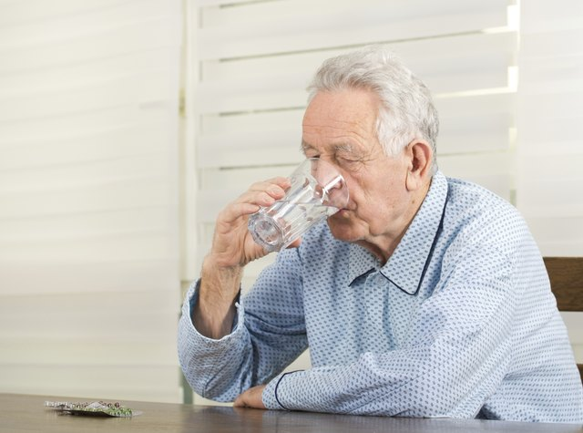Man taking medication with a glass of water