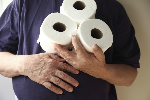 Man with upset stomach holding toilet paper rolls