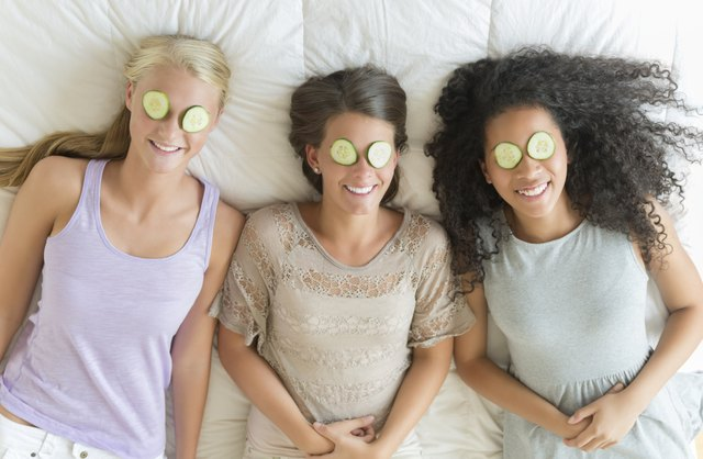 Three friends lay on a bed with cucumber slices over their eyes.