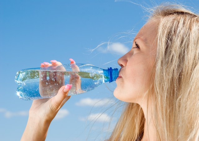 A woman drinking sparkling water.