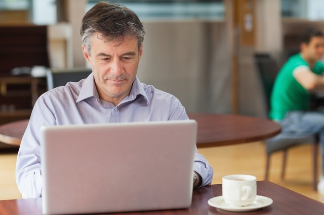Man working on computer while drinking coffee