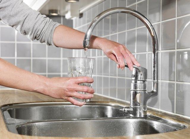 Frau gießt ein Glas Wasser