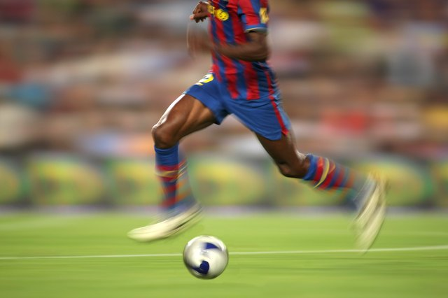 Legs of soccer player with ball