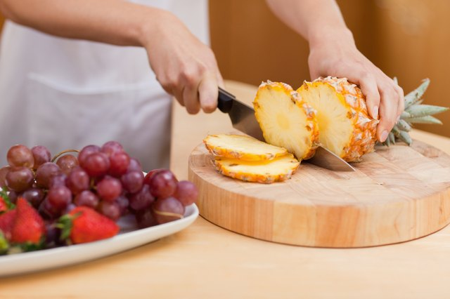 mother slicing pineapple and preparing fruit plate