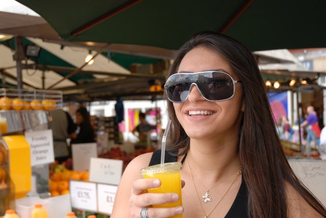 A woman drinks a cup of orange juice at an outdoor cafe.