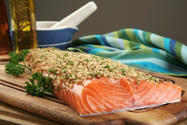 A filet of fresh salmon encrusted with chopped walnuts on a cutting board.
