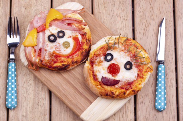 Two english muffin mini pizzas with faces.