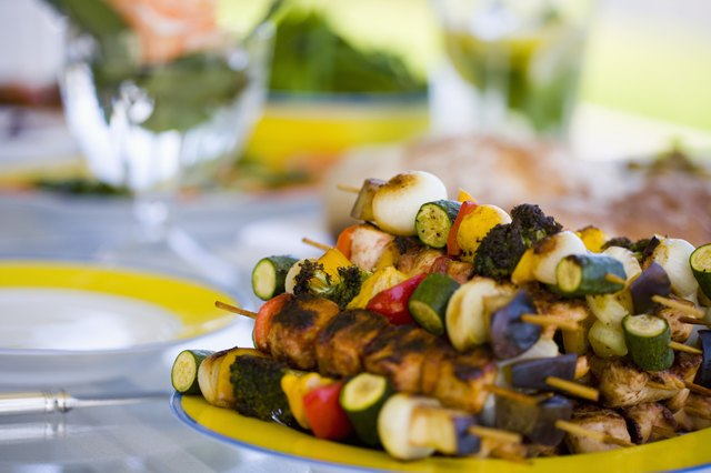 A plate of chicken and vegetable skewers.