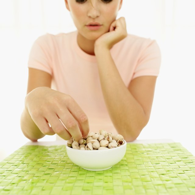 Young woman picking pistachios from a bowl.