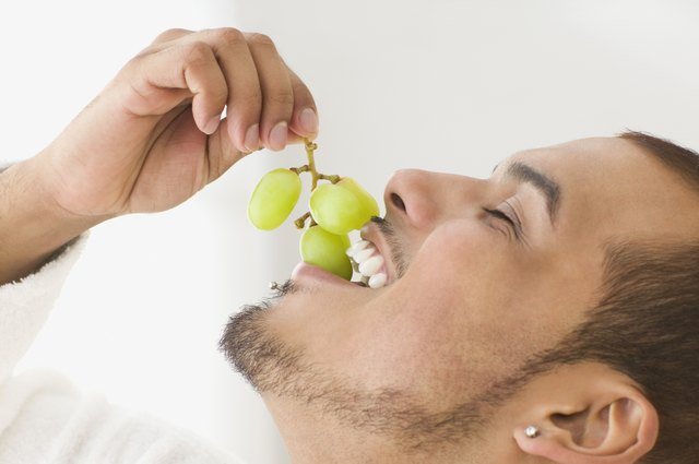 man eating grapes
