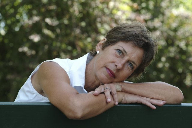 Middle-aged woman rests outside on a park bench