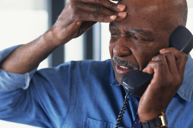Man with headache talking on phone at work