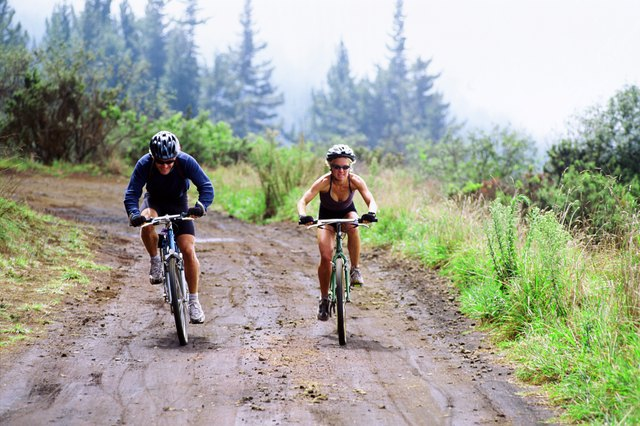 Couple on mountain bikes in forest