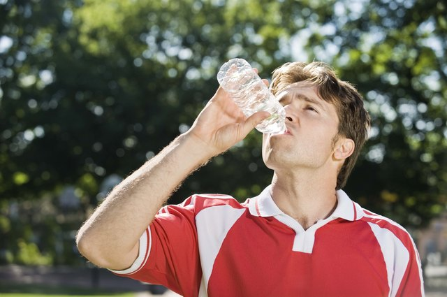 Soccer player drinking bottled water.