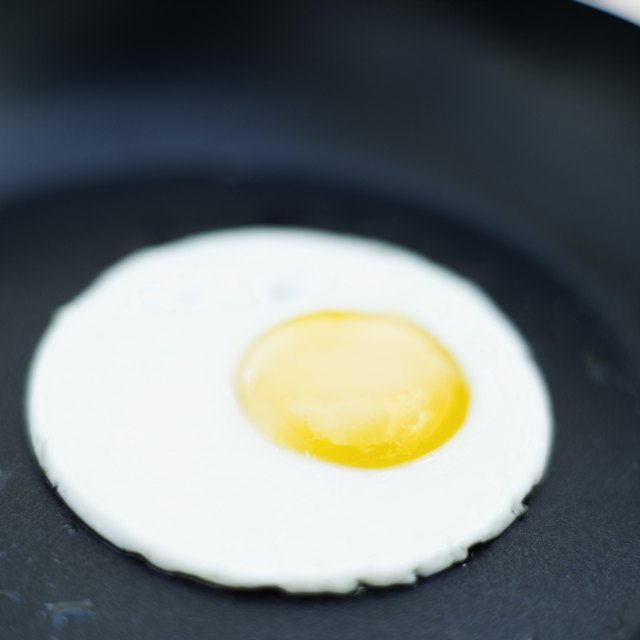 An egg fries in a pan.